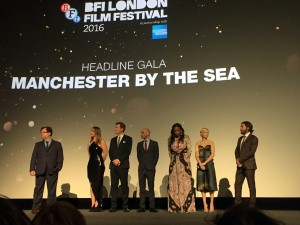 The cast of Manchester by the Sea dressed up for the release of the movie, standing under a title of the movie.
