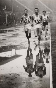 Three men running in a track covered with water puddles in the 1948 Olympic Games in London