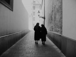 two nuns walking through an empty alleyway into light.