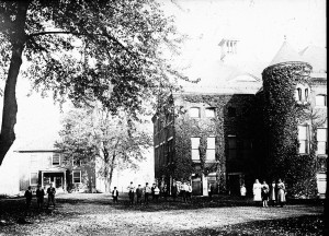 old black and white film photo of an old brick building to the right of the frame. small people in white stand in front of it. a large tree hangs over the top left half of the frame.