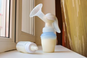 Breast pump and bottle of milk on the windowsill