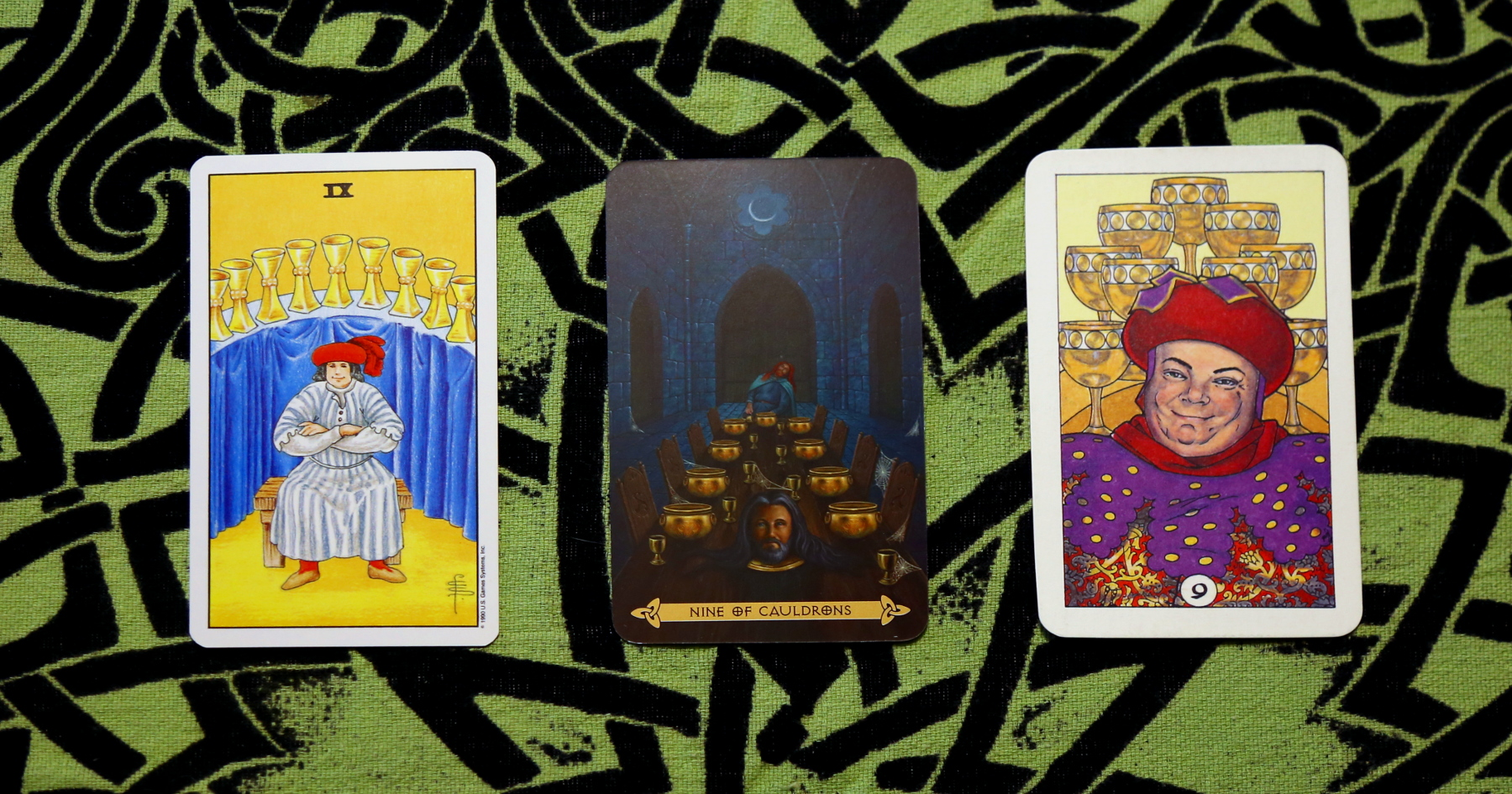 the Nine of Cups in the Rider-Waite-Smith Tarot, the Nine of Cauldrons in the Celtic Tarot, and the Nine of Cups in the Robin Wood Tarot