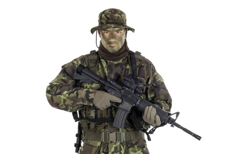 Soldier in camouflage and modern weapon M4. Isolated on white background