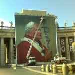 May 2, 2011 - Workers hang a large banner on Bernini's Colonnade, St. Peter's Basilica, to celebrate the Beatification of Pope John Paul II
