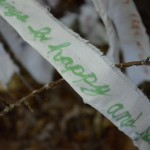 "Strip of white cloth tied to a branch reading ""all beings be happy and free"""