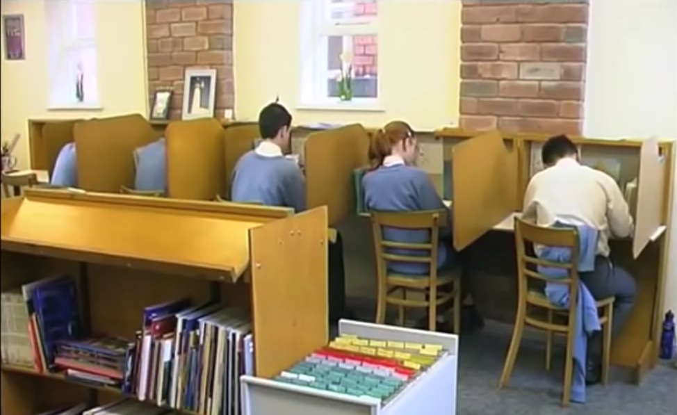 A row of four wooden desks, each separated by vertical screens. A child sits at each desk wearing a blue sweater.