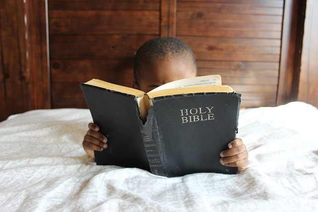 Boy reading Bible.