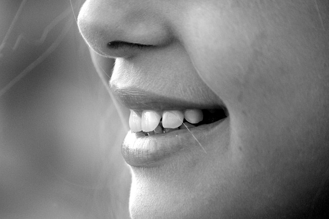 black and white photo of a child's smiling face from the bottom of her nose to the bottom of her chin.
