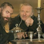 Jean Valjean (Hugh Jackman) and the Bishop (Colm Wilkinson) at dinner.