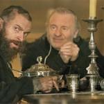 Jean Valjean (Hugh Jackman) and the Bishop (Colm Wilkinson) at dinner.