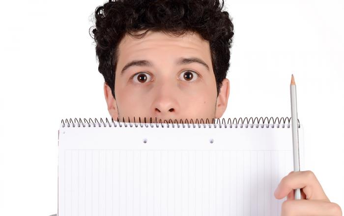 Close up of a young student holding notebook and pencil. Isolated white background.