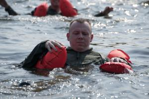 A member of the 133rd Airlift Wing is taking part in water survival training at the Army Training Site Arden Hills, Minnesota Sept. 16, 2012. The airman is using part of his survival vest to swim towards the safety of the life raft. U.S. Air Force photo by Airman 1st Class Kari L. Giles/released