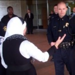 """A woman in a headscarf tries to get into the """"Human Rights Conference"""""""