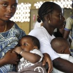 Women with their babies at a community health centre in Conakry, Guinea. Image via IRIN.