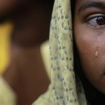 A Rohingya woman, displaced by recent violence in Kyukphyu township, Burma/Myanmar, cries after arriving at the Thaechaung refugee camp outside of Sittwe. Image by REUTERS/Soe Zeya Tun