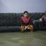 A family in Chittagong, Bangladesh sitting helplessly in their home submerged by flood water. Photograph: Jashim Salam/Demotix/Corbis
