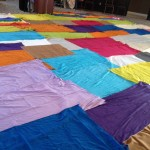 Fabrics laid out to create a bright and colourful prayer space.