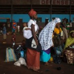 Having fled the continuing violence, displaced Muslim women and children are waiting in the hangar of Central African Republic's main airport to be evacuated to other African nations. Image by Siegfried Modola/Reuters.