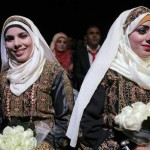 Two Palestinian brides sit on stage during a mass wedding in Jericho, West Bank where approx. 220 couples got married. Another 80 couples were married in Gaza; the ceremony was paid for by the Palestinian Presidential Office. Image by Ammar Awad/Reuters