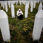 Bosnian Mejra Dzogaz prays near the graves of her family members at the Memorial Centre in Potocari, Bosnia-Herzegovina, where over 6,000 victims of the Srebrenica massacre have been buried. Image by Dado Ruvic/Reuters