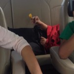 Lil D lying down in the back seat, arms drawn in, hood up, spinning his beads, at the end of a very long road trip.
