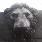 Around back of the sculpture, you might miss it if you're not careful, Aslan stares down from the wardrobe's ledge.