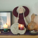 "Jacquelyn shares, ""This is my birth altar for my third baby. At the center is a Frigga doll by the lovely Dancing Goddess Dolls. A picture of me while pregnant with my 2nd, various birth goddess statues, candles (fire), a fan for labor (air), seashells (water), a decorated gourd rattle (earth) and birth jewelry I made for the journey. """