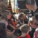 Michelle leading Water n Wax Scrying with Pagan kids, Pagan Alliance Witches' Ball, SF Bay Area 2012. Photo courtesy of Michelle Mueller.