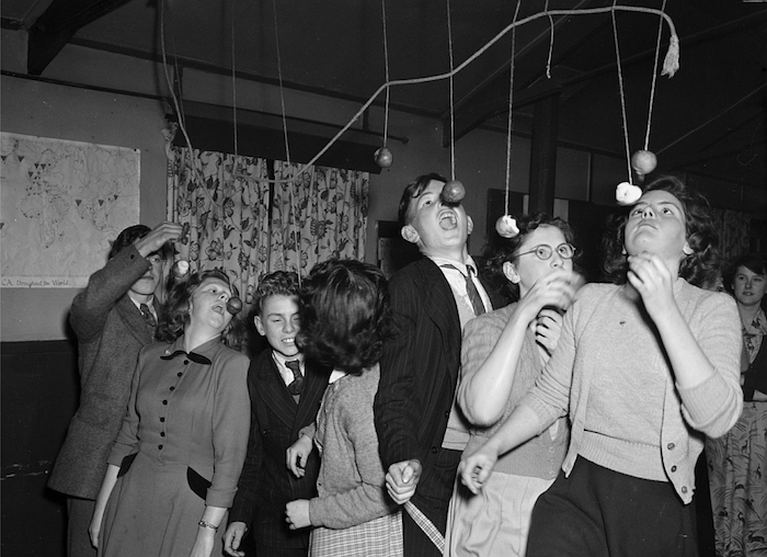 """""""Apple Bobbing"""" photo by Geoff Charles, from the National Library of Wales, CC0 1.0 Universal."""