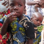Primary girl with baby sibling in Likasi, Democratic Republic of the Congo.