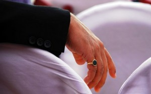A man wearing a gemstone ring on his pinky.