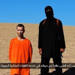 An ISIS executioner stands beside British aid worker David Haines.
