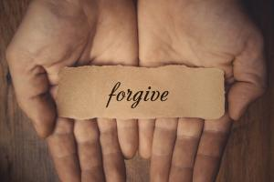 Hands holding piece of paper with word Forgive