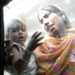 A woman comes up to our car window begging for money. (New Delhi)
