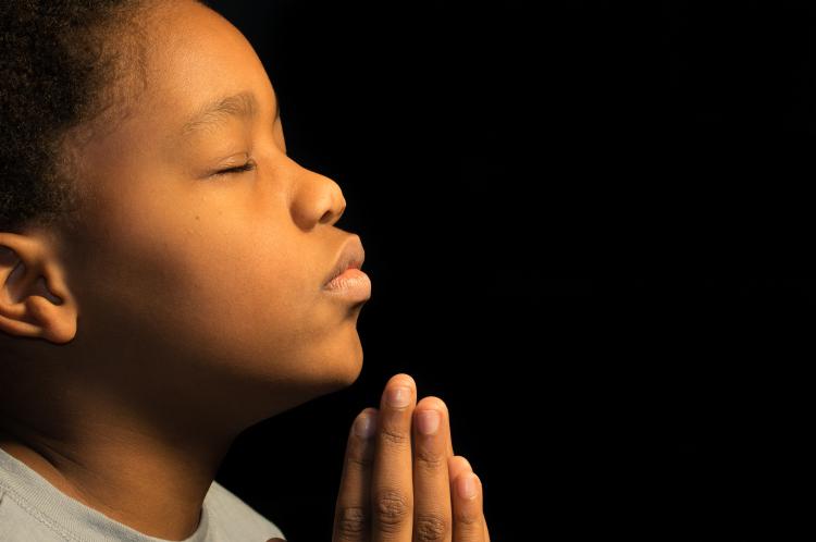 Young boy praying. (photo by Damon Yancy/Shutterstock)
