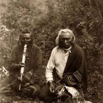 Two Crow Indians sitting on the ground smoking a peace pipe.