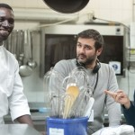 "From left, actor Omar Sy and directors Olivier Nakache and Eric Toledano discuss a scene on the set of ""Samba."" (Broad Green Pictures/David Koskas)"