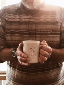 Owner of Coffeehouse hold a cup of coffee.