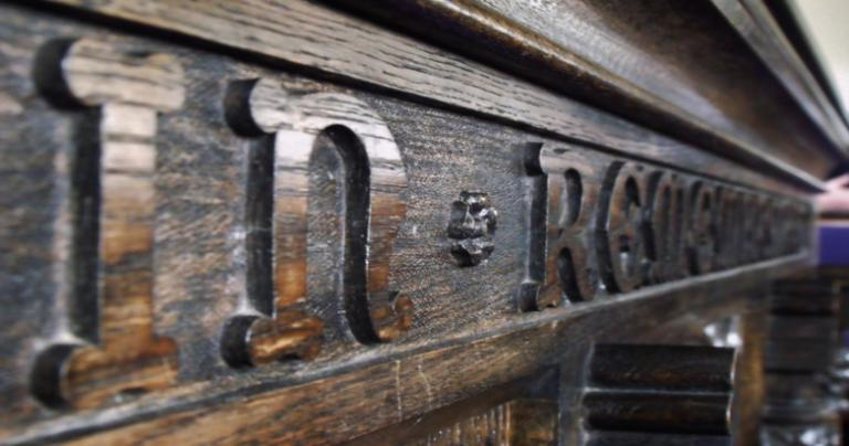 """Close up picture of """"In Remembrance"""" on a communion table"""