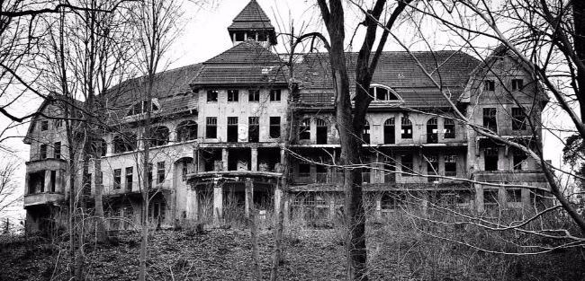 Black and white photograph of a dilapidated 3 story sprawling wooden mansion. The lifeless trees and empty windows only make it creepier.