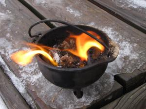 A small cauldron sits on the corner of an icy porch. A tiny fire is burning within it.