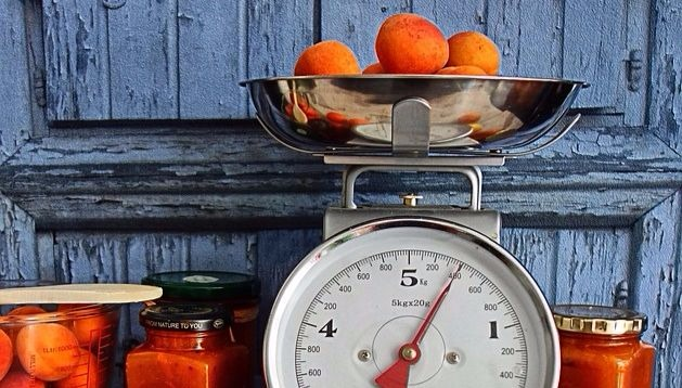 A worn painted blue door stands behind a harvest of peaches. A metal scale is weighing some while others are already canned or turned into jelly.