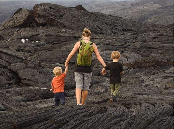 Mom and two boys walk across lava fields