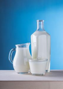 a pitcher, a bottle and a glass filled with white milk