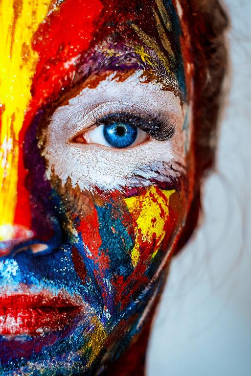 a woman's face half on-camera, covered in paint splatters, with a single blue eye