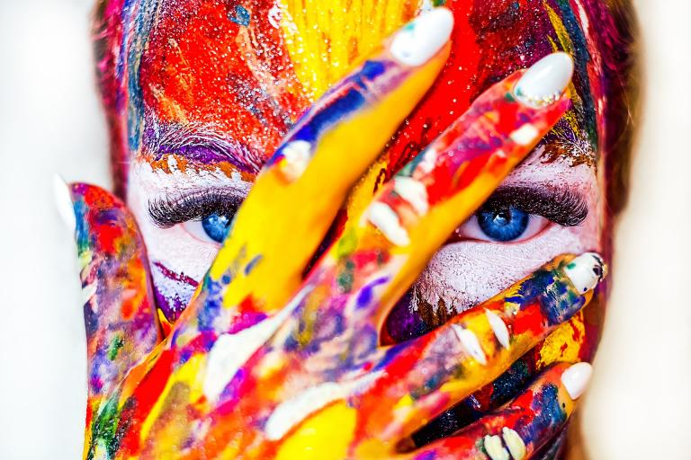 a woman covering her face with her hand, revealing streaks of paint and very blue eyes