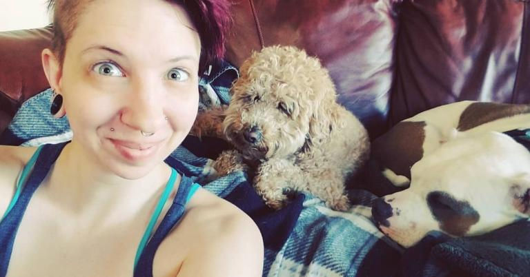myself, a femme with red-purple hair, smiling into the camera while a brown goldendoodle and a pit bull cuddle behind me