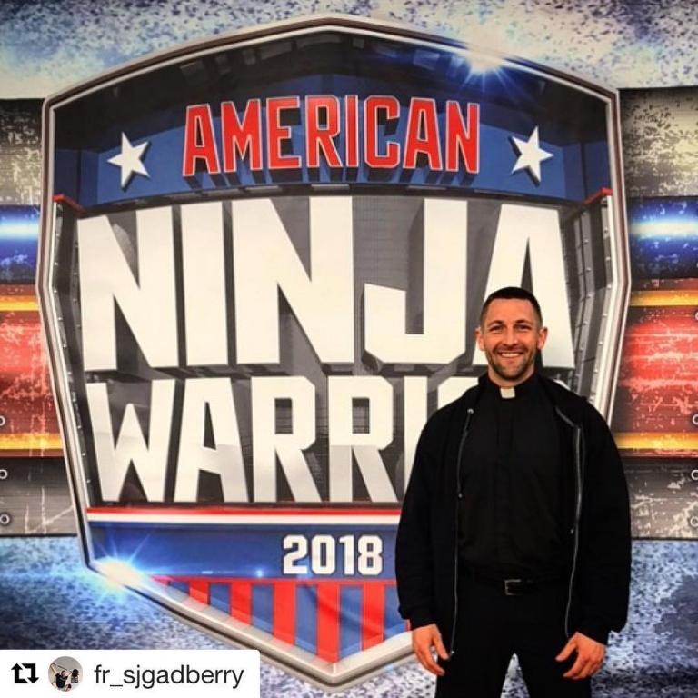 Fr Stephen in front of the American Ninja Warrior logo