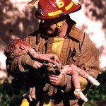 The Fifth Station: Fire Capt. Chris Fields cradles Baylee Almon on April 19, 1995, in Oklahoma City. Photo by Charles Porter.