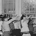 American school students salute the flag in what is meant to be a not-at-all creepy  mandatory daily recitation of a loyalty oath. The original salute accompanying the pledge was abandoned in the 1940s for some reason, replaced with the current still-mandatory hand-on-the-heart.